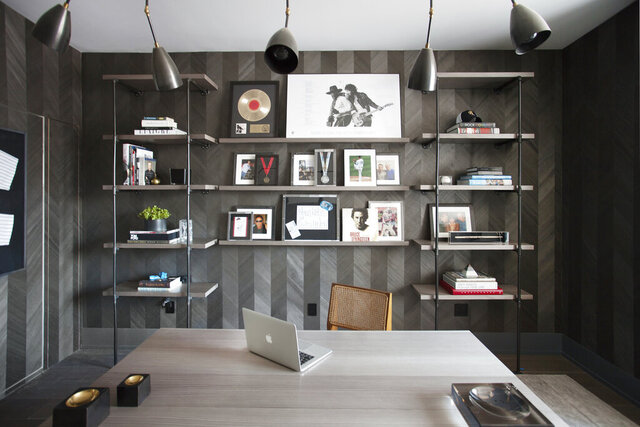 This 2015 photo shows a home office designed by interior designer Michelle Gerson in New York. When one partner has a collection to display and the other partner prefers an uncluttered space, it's important to take an organized approach, as seen in this home office space created by Gerson, where custom shelving was designed to prominently but neatly display a collection of music memorabilia. (Patrick Cline/Michelle Gerson via AP)