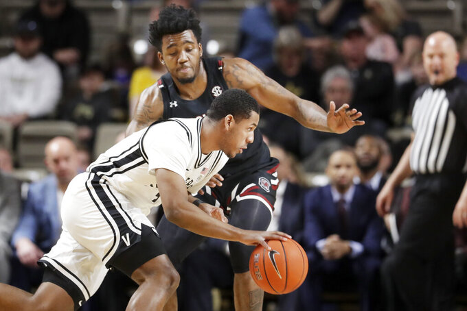 Vanderbilt's Jordan Wright, front, drives against South Carolina's Jermaine Couisnard in the first half of an NCAA college basketball game Saturday, March 7, 2020, in Nashville, Tenn. (AP Photo/Mark Humphrey)
