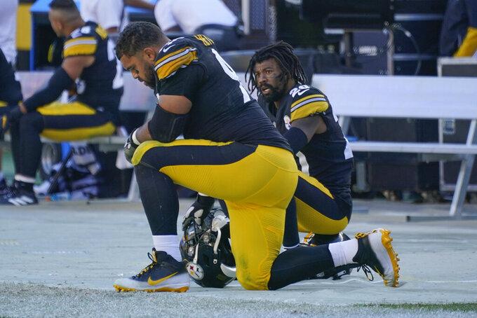 Pittsburgh Steelers defensive end Cameron Heyward, left, kneels on the sideline as his team is losing to the Cincinnati Bengals during the second half an NFL football game, Sunday, Sept. 26, 2021, in Pittsburgh. (AP Photo/Gene J. Puskar)