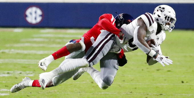 Mississippi State tight end Farrod Green (82) pulls in a pass reception against Mississippi defensive back Zedrick Woods (36) during the first half of an NCAA college football game in Oxford, Miss., Thursday, Nov. 22, 2018. (AP Photo/Rogelio V. Solis)