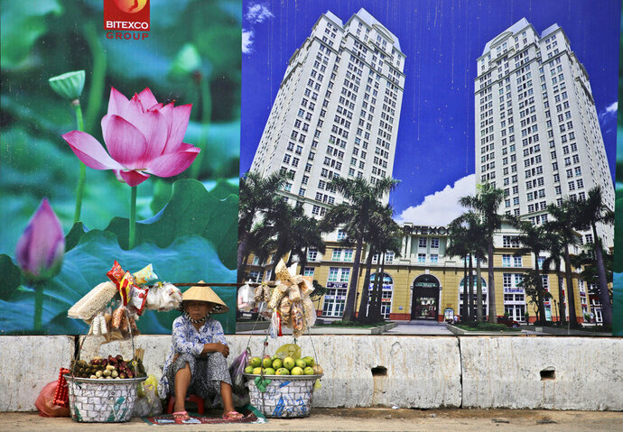 FILE - In this April 29, 2015, file photo, a snack and fruit vendor waits for customers near the advertisement board of a shopping mall and apartment building in Ho Chi Minh City, Vietnam. Vietnam, the location of U.S. President Donald Trump's next meeting with North Korean leader Kim Jong Un, has come a long way since the U.S. abandoned its war against communist North Vietnam in the 1970s. (AP Photo/Dita Alangkara, File)