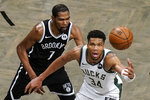 Brooklyn Nets' Kevin Durant (7) defends against Milwaukee Bucks' Giannis Antetokounmpo (34) during overtime of Game 7 of a second-round NBA basketball playoff series Saturday, June 19, 2021, in New York. (AP Photo/Frank Franklin II)