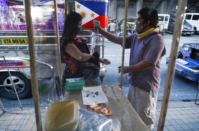 A passenger has her temperature checked to prevent the spread of the new coronavirus as some routes for the Traditional Jeepney buses were opened to help public transportation while the government slowly eases lockdown in metropolitan Manila, Philippines on Friday, July 3, 2020. (AP Photo/Aaron Favila)