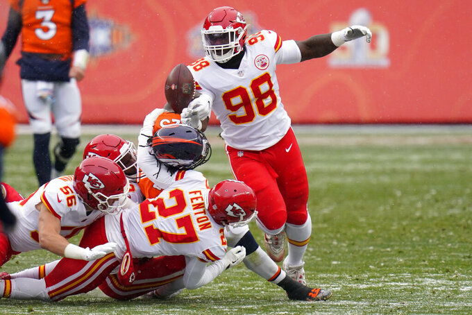 Denver Broncos running back Melvin Gordon fumbles the ball as he is hit by Kansas City Chiefs cornerback Rashad Fenton (27) and others during the first half of an NFL football game Sunday, Oct. 25, 2020, in Denver. (AP Photo/Jack Dempsey)