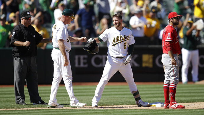 Oakland Athletics' Robbie Grossman (8) is congratulated by third base coach Matt Williams after hitting a two-run triple off Los Angeles Angels' Adalberto Mejia in the seventh inning of a baseball game Thursday, Sept. 5, 2019, in Oakland, Calif. (AP Photo/Ben Margot)