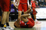 Ball State guard Ishmael El-Amin (5) reacts on the floor after being hit during the second half of an NCAA college basketball game against Washington, Sunday, Dec. 22, 2019, in Honolulu. (AP Photo/Marco Garcia)