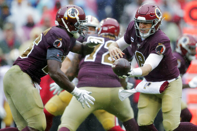 FILE - In this Sunday, Oct. 20, 2019, file photo, Washington Redskins quarterback Case Keenum, right, hands off to Washington Redskins running back Adrian Peterson in the first half of an NFL football game against the San Francisco 49ers in Landover, Md. Kirk Cousins prepares to face his former team, and Keenum and Peterson get ready to do the same, as the Minnesota Vikings try to keep their momentum going against the woeful Washington Redskins.(AP Photo/Julio Cortez, File)
