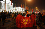 Two men hold the old national flag as opposition supporters gather to protest the leftist government policy towards Bulgaria, in front of the government building in Skopje, North Macedonia, late Thursday, Nov. 26, 2020. Main conservative opposition leader Hristijan Mickoski has called late on Thursday leftist Prime minister Zoran Zaev to resign after his controversial interview given to one Bulgarian media in which he mitigated Bulgaria's occupation role in then Macedonia during the World War II. (AP Photo/Boris Grdanoski)
