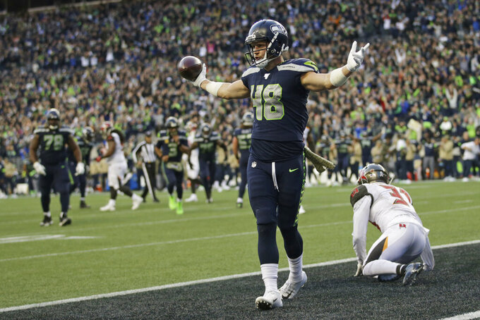 Seattle Seahawks tight end Jacob Hollister (48) stands above Tampa Bay Buccaneers free safety Jordan Whitehead, right, after scoring a touchdown in overtime of an NFL football game, Sunday, Nov. 3, 2019, in Seattle. (AP Photo/Scott Eklund)