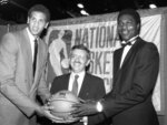 FILE - In this June 19, 1984 file photo, NBA commissioner David Stern, center, is flanked by Akeem Olajuwon, right, the No. 1 pick overall by the Houston Rockets, and Sam Bowie, the No. 2 pick overall by the Portland Trail Blazers at the NBA Draft in New York. David Stern, who spent 30 years as the NBA's longest-serving commissioner and oversaw its growth into a global power, has died on New Year's Day, Wednesday, Jan. 1, 2020. He was 77. (AP Photo/Marty Lederhandler, File)