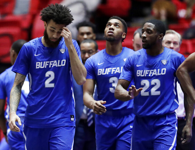 Buffalo guard Jeremy Harris (2), guard Jayvon Graves (3) and guard Dontay Caruthers (22) react as they walk on the court during the second half of an NCAA college basketball game against Northern Illinois, Tuesday, Jan. 22, 2019, in DeKalb, Ill. Northern Illinois won 77-75. (AP Photo/Nam Y. Huh)
