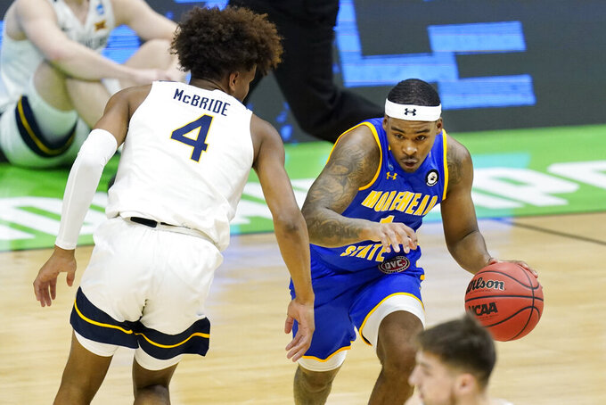 Morehead State's DeVon Cooper, right, drives against West Virginia's Miles McBride (4) during the first half of a college basketball game in the first round of the NCAA tournament at Lucas Oil Stadium Friday, March 19, 2021, in Indianapolis. (AP Photo/Mark Humphrey)