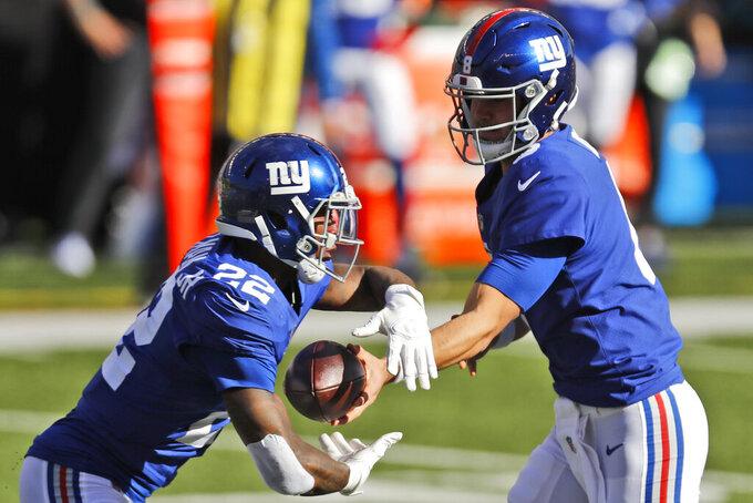 New York Giants quarterback Daniel Jones (8) hands off the ball to running back Wayne Gallman (22) during the first half of NFL football game against the Cincinnati Bengals, Sunday, Nov. 29, 2020, in Cincinnati. (AP Photo/Aaron Doster)