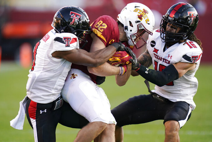 Iowa State wide receiver Landen Akers (82) is tackled by Texas Tech defensive back Zech McPhearson, left, and defensive back Thomas Leggett, right, after catching a pass during the second half of an NCAA college football game, Saturday, Oct. 10, 2020, in Ames, Iowa. Iowa State won 31-15. (AP Photo/Charlie Neibergall)