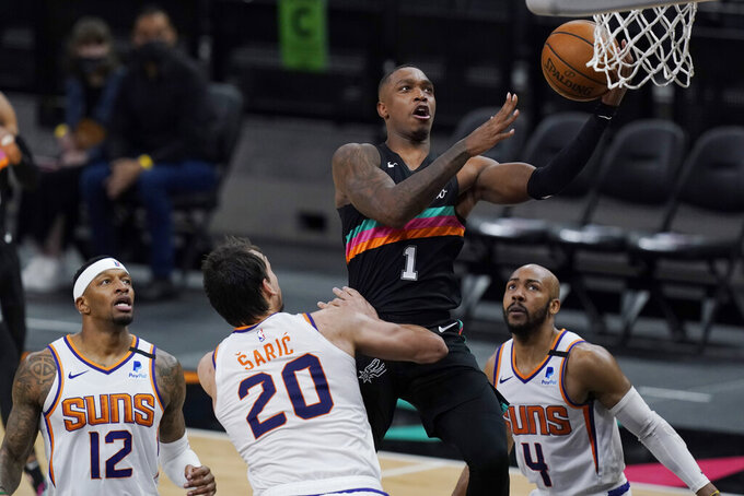 San Antonio Spurs guard Lonnie Walker IV (1) scores over Phoenix Suns forward Dario Saric (20) and guard Jevon Carter (4) during the second half of an NBA basketball game in San Antonio, Sunday, May 16, 2021. (AP Photo/Eric Gay)
