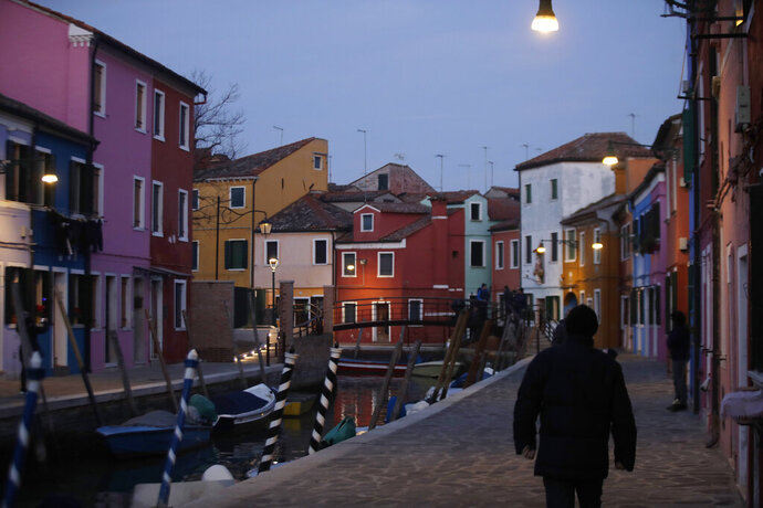 In this image taken on Thursday, Jan. 16, 2020, people walk at the Burano island, Italy. The Venetian island of Burano's legacy as a fishing village remains the source of its charms: the small colorful fishermen's cottages, traditional butter cookies that were the fishermen's sustenance at sea and delicate lace still stitched by women in their homes. As the island's population dwindles, echoing that of Venice itself, so too are the numbers of skilled artisans and tradespeople who have kept the traditions and economy alive. (AP Photo/Luca Bruno)
