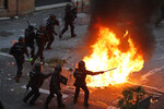 Police officers run past a burning barricade on the fifth day of protests over the conviction of a dozen Catalan independence leaders in Barcelona, Spain, Friday, Oct. 18, 2019. Tens of thousands of flag-waving demonstrators demanding Catalonia's independence and the release from prison of their separatist leaders have flooded downtown Barcelona. The protesters have poured into the city after some of them walked for three days in
