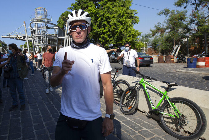 """Former American professional cyclist Lance Armstrong, center, prepares to ride with Lebanese and foreign cyclists at the site of the Aug. 4 deadly blast in the port of Beirut that killed scores and wounded thousands in Beirut, Lebanon, Sunday, Oct. 4, 2020. Armstrong led a charity bike tour named """"Bike for Beirut,"""" to raise awareness and fund organizations that are helping residents of the Lebanese capital who suffered losses as a result of the massive blast. (AP Photo/Hassan Ammar)"""
