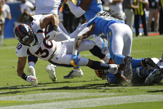 Denver Broncos running back Phillip Lindsay scores past Los Angeles Chargers defensive back Rayshawn Jenkins during the first half of an NFL football game Sunday, Oct. 6, 2019, in Carson, Calif. (AP Photo/Marcio Jose Sanchez)