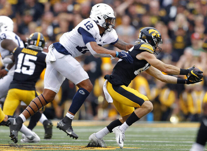 Iowa wide receiver Charlie Jones (16) makes a reception in front of Penn State linebacker Brandon Smith (12) during the first half of an NCAA college football game, Saturday, Oct. 9, 2021, in Iowa City, Iowa. (AP Photo/Matthew Putney)