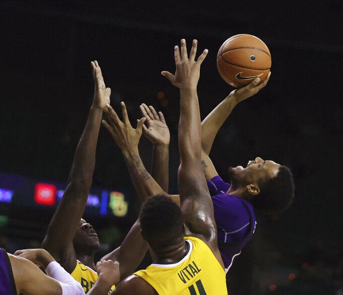 Stephen F. Austin forward Calvin Solomon, right, is fouled while shooting past Baylor guard Mark Vital, right, during the first half of an NCAA college basketball game Wednesday, Dec. 9, 2020, in Waco, Texas. (Rod Aydelotte/Waco Tribune Herald via AP)
