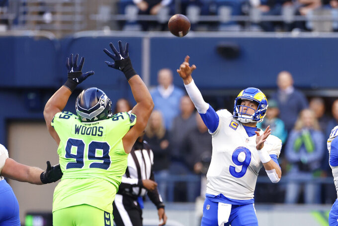 Los Angeles Rams quarterback Matthew Stafford (9) passes under pressure from Seattle Seahawks defensive tackle Al Woods (99) during the first half of an NFL football game, Thursday, Oct. 7, 2021, in Seattle. (AP Photo/Craig Mitchelldyer)