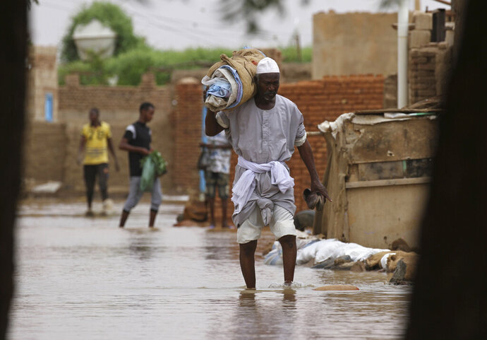 A man carries belongings as he wades through of a flooded road in the town of Shaqilab, about (25 km) southwest of the capital, Khartoum, Sudan, Monday, Aug. 31, 2020. (AP Photo/Marwan Ali)