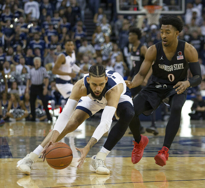 Nevada forward Cody Martin (11) beats San Diego State guard Devin Watson (0) to a loose ball in the first half of an NCAA college basketball game in Reno, Nev., Saturday, March 9, 2019. (AP Photo/Tom R. Smedes)