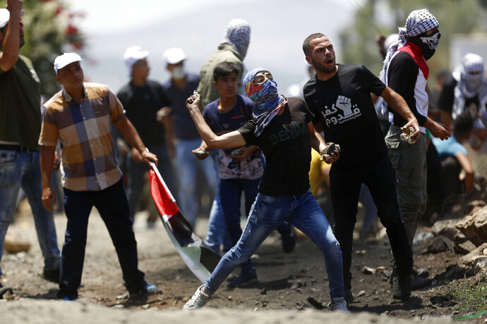 Palestinian demonstrators hurl stones at Israeli troops during a protest Israel's plan to annex parts Israel's plan to annex parts of the West Bank and Trump's mideast initiative, in the West Bank village of Kufr Qaddumm near Nablus, Friday, July 3, 2020.(AP Photo/Majdi Mohammed)