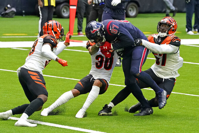 Houston Texans tight end Darren Fells (87) drives toward the end zone for a touchdown after making a catch as Cincinnati Bengals' Germaine Pratt (57), Jessie Bates III (30) and LeShaun Sims (38) try to tackle him during the second half of an NFL football game Sunday, Dec. 27, 2020, in Houston. (AP Photo/Sam Craft)