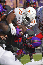Texas defensive lineman Keondre Coburn (99) tackles TCU running back Darius Anderson (6) in the first half of an NCAA college football game in Fort Worth, Texas, Saturday, Oct. 26, 2019. (AP Photo/Louis DeLuca)