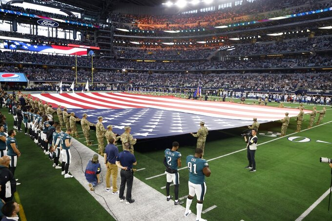 An American flag is unfurled on the field before the first half of an NFL football game between the Philadelphia Eagles and Dallas Cowboys in Arlington, Texas, Monday, Sept. 27, 2021. (AP Photo/Michael Ainsworth)