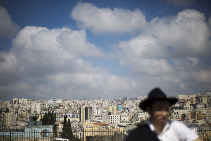 In this Wednesday, March 6, 2019 photo, a Jewish man visits the Israeli controlled part of the West Bank city of Hebron, in the West Bank. The Falic family of Florida, owners of the ubiquitous chain of Duty Free Americas shops, funds a generous and sometimes controversial philanthropic empire in Israel that runs through the corridors of power and stretches deep into the occupied West Bank. An Associated Press investigation shows that the family has donated at least $5.6 million to settler groups in the West Bank and east Jerusalem over the past decade, funding synagogues, schools and social services, along with causes considered extreme even in Israel.  (AP Photo/Ariel Schalit)