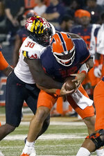 Maryland linebacker Durell Nchami sacks Illinois quarterback Brandon Peters during the first half of an NCAA college football game Friday, Sept. 17, 2021, in Champaign, Ill. (AP Photo/Charles Rex Arbogast)