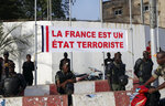 In this photo taken on Friday, Nov. 15, 2019, Malian soldiers stand under a banner that reads '' France is a terrorist State '' during a protest at the Independence square in Bamako, Mali. Mali's military has abandoned some of its most isolated outposts in the desert north while extremist attacks have killed more than 100 soldiers in just six weeks. The West African nation's president faces a decline in military morale, a sentiment that helped spark a coup against his predecessor in 2012. (AP Photo/Baba Ahmed)