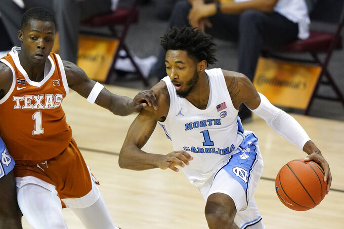 North Carolina guard Leaky Black (1) drives the ball against Texas guard Andrew Jones (1) in the first half of an NCAA college basketball game for the championship of the Maui Invitational, Wednesday, Dec. 2, 2020, in Asheville, N.C. (AP Photo/Kathy Kmonicek)