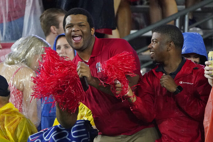 Mississippi fans brave a pregame rain prior to an NCAA college football game between Tulane and Mississippi, Saturday, Sept. 18, 2021, in Oxford, Miss. A weather delay was called by officials. (AP Photo/Rogelio V. Solis)
