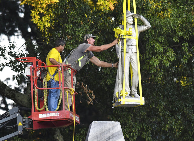 The Confederate statue located in the Circle at the University of Mississippi is lowered to the ground as part of the process to move it to the Confederate Soldiers Cemetery on campus, in Oxford, Miss. Tuesday, July 14, 2020. (Bruce Newman/The Oxford Eagle via AP)