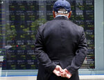 A man looks at an electronic stock board of a securities firm in Tokyo, Monday, May 20, 2019. Shares are mixed in Asia, with India and Australia leading gains following elections that look set to keep incumbents in office. (AP Photo/Koji Sasahara)