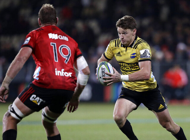 FILE - In this June 29, 2019, file photo, Hurricanes Beauden Barrett, right, runs at Crusaders Luke Romano during the Super Rugby semifinal between the Crusaders and the Hurricanes in Christchurch, New Zealand. The cheers of the crowd will resound in New Zealand sports stadiums for the first time in months with more than 50,000 people expected to attend matches in the opening round of Super Rugby Aotearoa. More than 18,000 are expected at the first match in the New Zealand professional rugby tournament in Dunedin on Saturday, June 13, 2020 between the Highlanders and the Hamilton-based Chiefs. (AP Photo/Mark Baker,File)