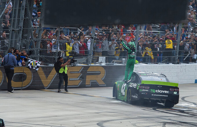 Kyle Larson stands on his car and waves to crowd after winning the NASCAR Cup Series playoff auto race Sunday, Oct. 6, 2019, at Dover International Speedway in Dover, Del. (AP Photo/Jason Minto)