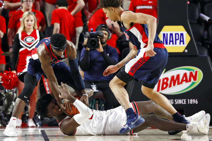 Mississippi guard Terence Davis, left, and Georgia forward Rayshaun Hammonds (20) vie for the ball during an NCAA college basketball game in Athens, Ga., on Saturday, Feb. 9, 2019. (Joshua L. Jones/Athens Banner-Herald via AP)