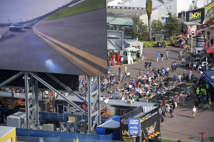 Spectators watch from a giant infield video monitor during a NASCAR Xfinity Series auto race at Daytona International Speedway Saturday, Feb. 16, 2019, in Daytona Beach, Fla. (AP Photo/Phelan M. Ebenhack)