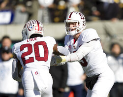 Stanford quarterback K.J. Costello (3) hands off toe running back Bryce Love (20) against the California  in the first quarter of a football game in Berkeley, Calif., Saturday, Dec. 1, 2018. (AP Photo/John Hefti)