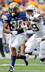 Pittsburgh running back Qadree Ollison (30) breaks fee from Georgia Tech defensive back Tariq Carpenter on his way to a touchdown run in the first quarter of an NCAA football game, Saturday, Sept. 15, 2018, in Pittsburgh. (AP Photo/Keith Srakocic)