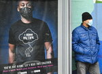 A man wearing a protective mask waits for a city bus during the COVID-19 pandemic in Toronto on Tuesday, Dec. 1, 2020. Toronto and Peel region continue to be in lockdown. (Nathan Denette/The Canadian Press via AP)