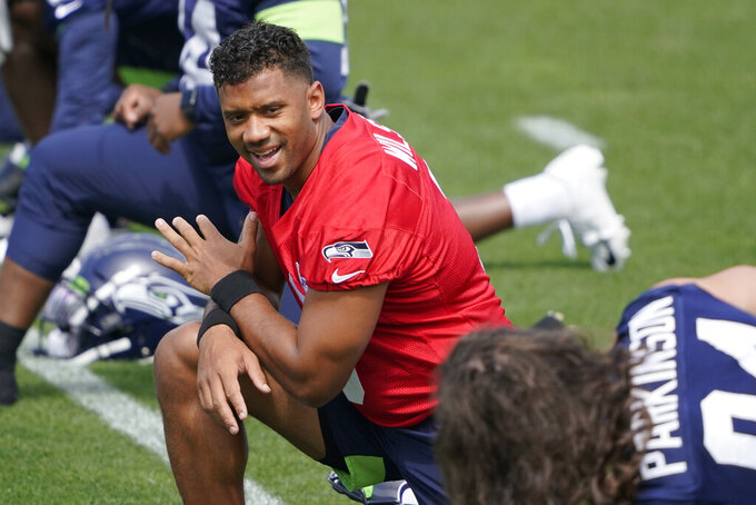 Seattle Seahawks quarterback Russell Wilson stretches at the start of NFL football practice Tuesday, June 8, 2021, in Renton, Wash. (AP Photo/Ted S. Warren)
