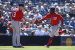 Washington Nationals' Howie Kendrick, right, is congratulated by third base coach Bob Henley after hitting a home run during the eighth inning of a baseball game against the San Diego Padres, Sunday, June 9, 2019, in San Diego. (AP Photo/Orlando Ramirez)