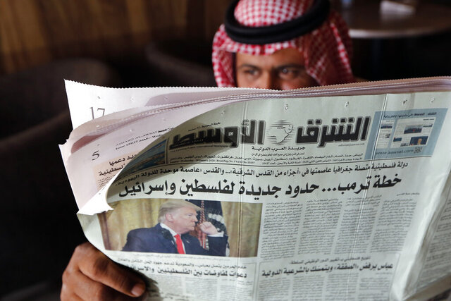 A man holds the daily Asharq Al-Awsat newspaper fronted by a picture of President Donald Trump, at a coffee shop in Jiddah, Saudi Arabia, Wednesday, Jan. 29, 2020. U.S. President Donald Trump unveiled his long-awaited Mideast peace plan Tuesday alongside a beaming Benjamin Netanyahu, presenting a vision that matched the Israeli leader's hard-line, nationalist views while falling far short of Palestinian ambitions. Arabic reads