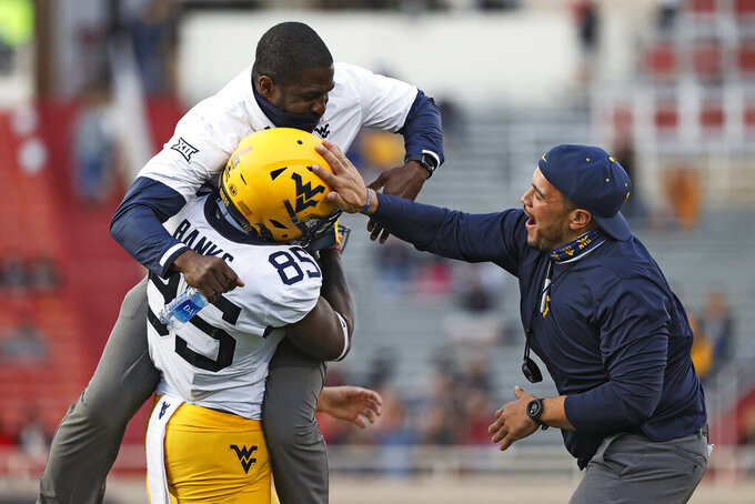 West Virginia strength coaches Rafael Horton and Alex Mitchell celebrate with T.J. Banks (85) after he scored a touchdown during the second half of an NCAA college football game against Texas Tech, Saturday, Oct. 24, 2020, in Lubbock, Texas. (AP Photo/Brad Tollefson)